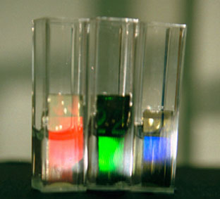 The slide is sliced up and placed in a sample liquid in a cuvette. As the substance in the liquid alters then the replay colour of the hologram may change. In the 3 cuvettes shown, the same polymer material is contracting from left to right.